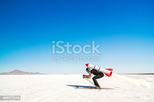 Mid adult man on skis with a rocket on his back in the middle of the desert getting ready for lift off into the unknown in pursue of new horizons. Plenty of copyspace, blue clear sky.