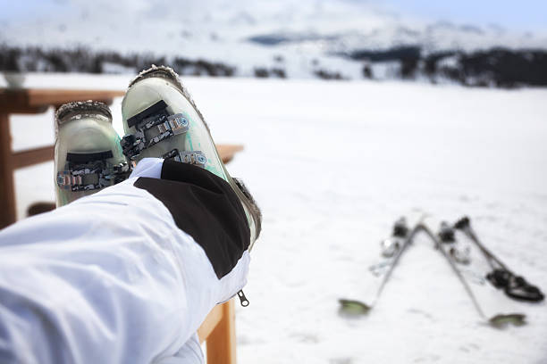 Skier with feet up and skis in background Skier relaxing with her feet up in a mountain restaurant.  Defocussed skis and mountains in background. apres ski stock pictures, royalty-free photos & images