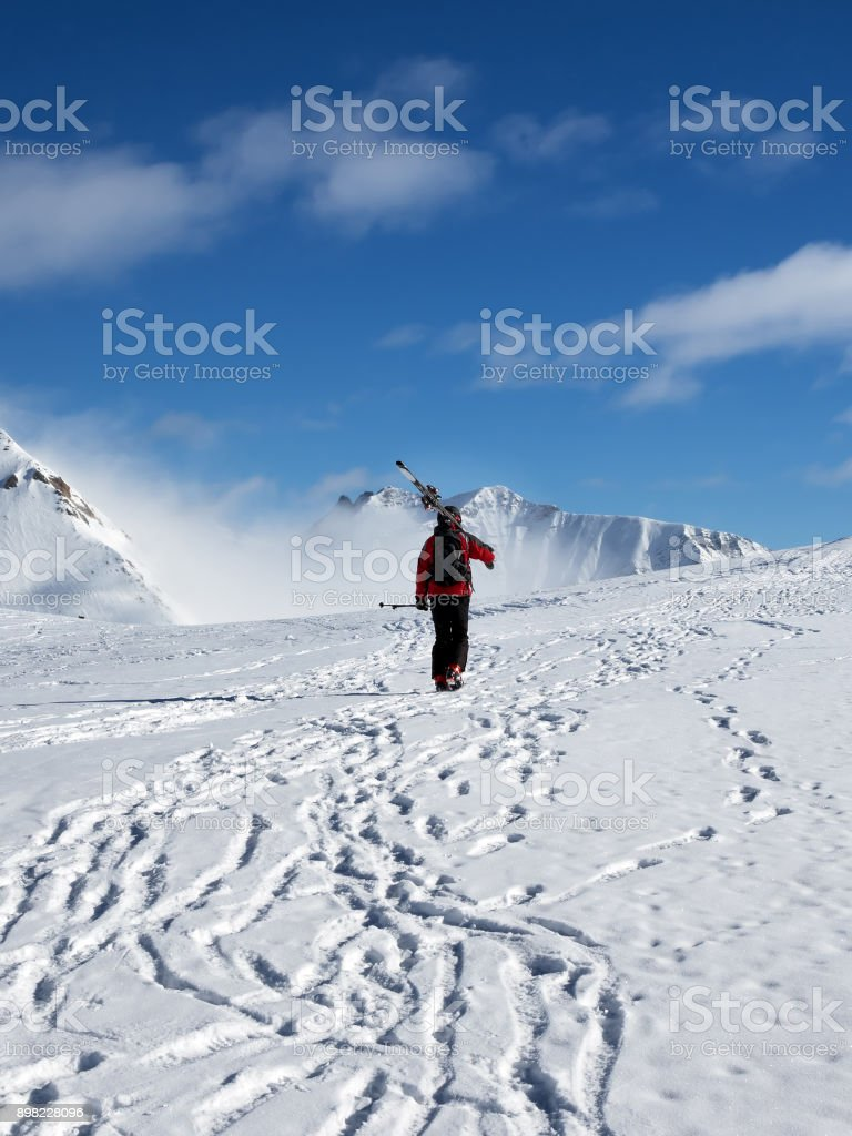Skier with skis go up to top of snowy mountain stock photo