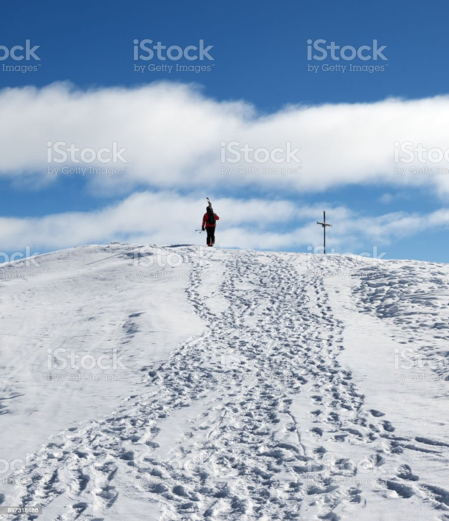 Skier with skis on his shoulder go up to top of snowy mountain stock photo