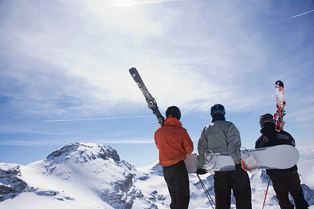 Skiers and a snowboarder on a mountain carrying their equipment stock photo
