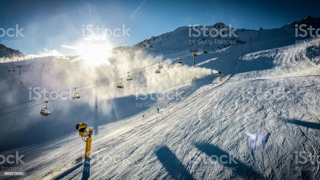 Skiers and chairlifts at sunset in Alpine ski resort . Artistic HDR image. stock photo