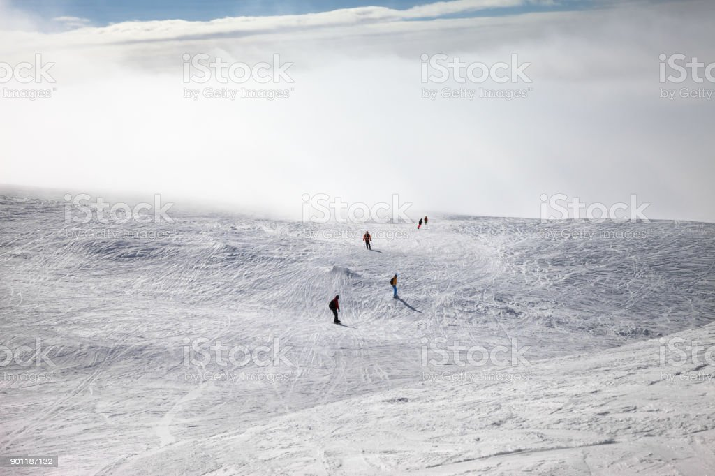 Skiers and snowboarders downhill on snowy slope and sunlight sky in haze stock photo