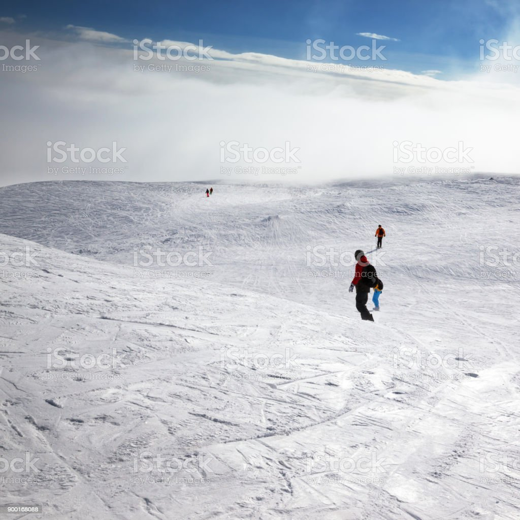 Skiers and snowboarders downhill on snowy slope stock photo