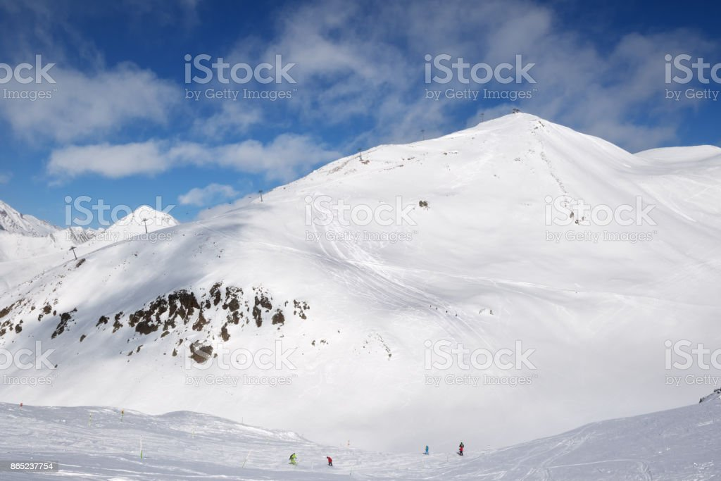 Skiers and snowboarders downhill on trace and mountains with clouds stock photo
