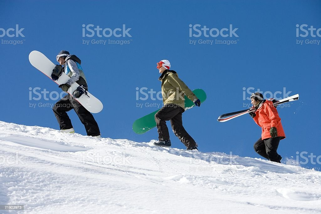 Skiers and snowboarders going up mountain royalty-free stock photo