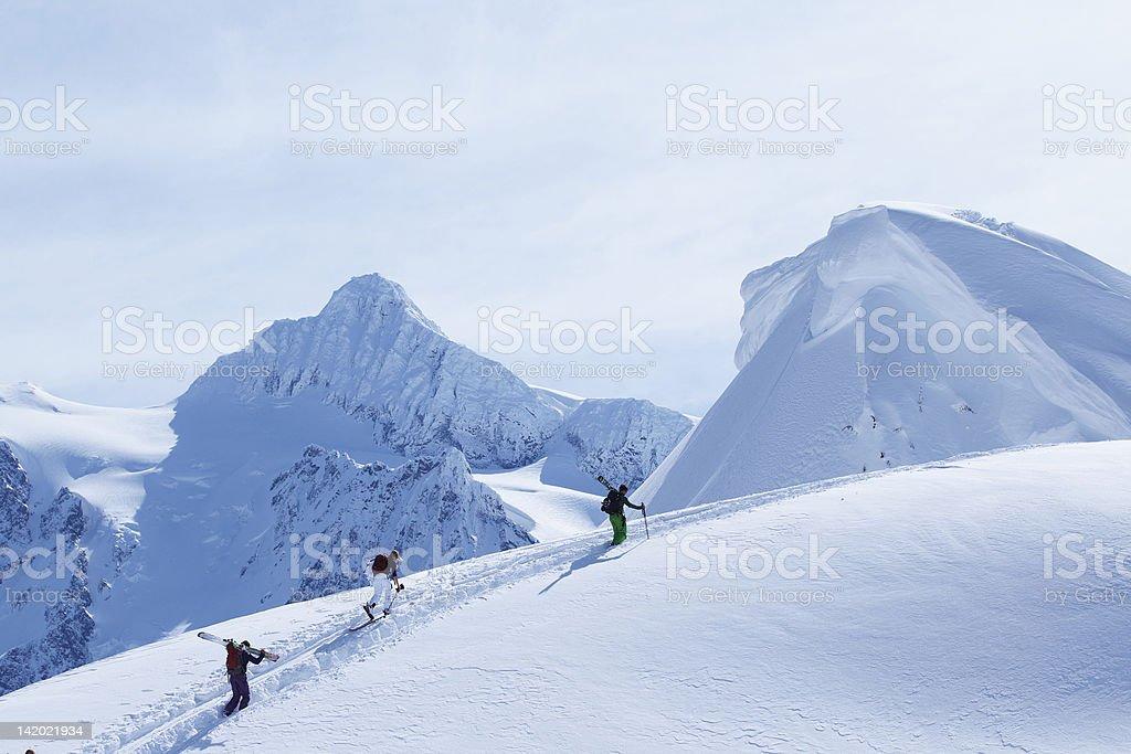 Skiers climbing snowy slope stock photo