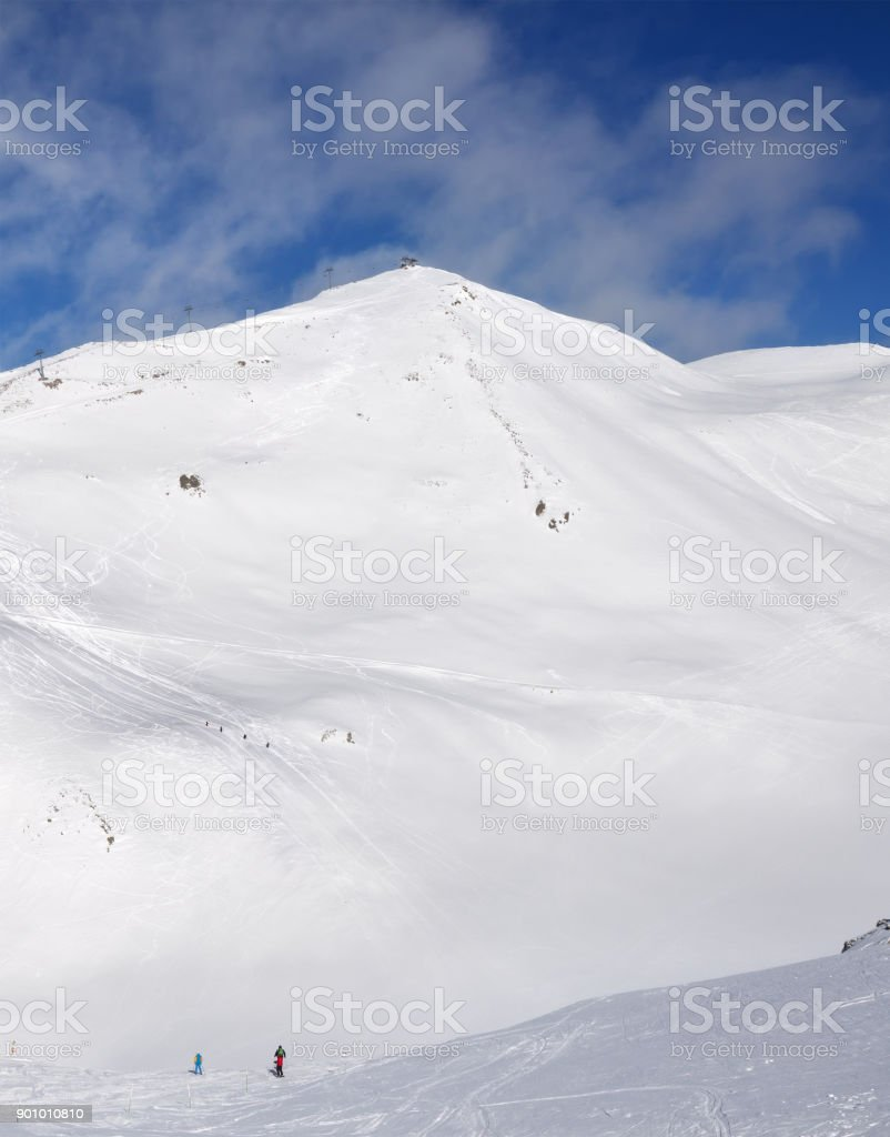 Skiers downhill on snowy freeride trace and mountains with clouds stock photo