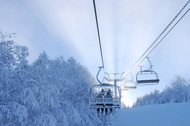 Skiers in chairlift withsunset. Skiers in chairlift withsunset, trees full of snow,Mount Sutton, Quebec, Canada apres ski stock pictures, royalty-free photos & images