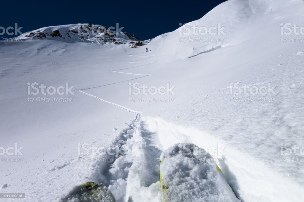Skiers laying down switchback touring tracks to mountain pass stock photo