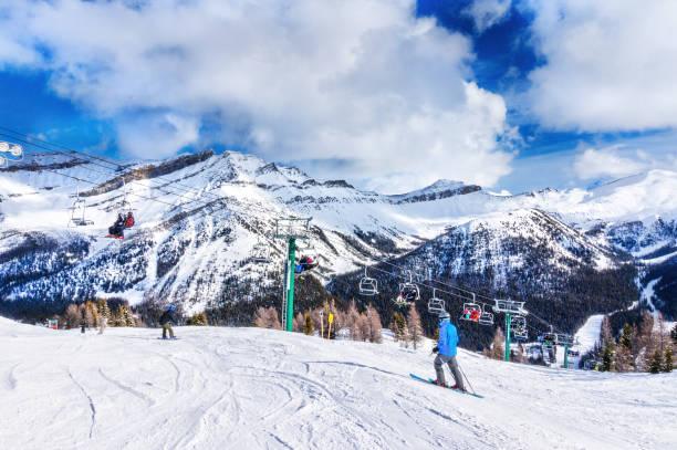 skiërs op stoeltjeslift omhoog een skipiste in de canadese rockies - lake louise stockfoto's en -beelden