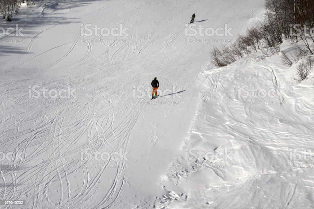Skiers on ski slope at sun winter day stock photo