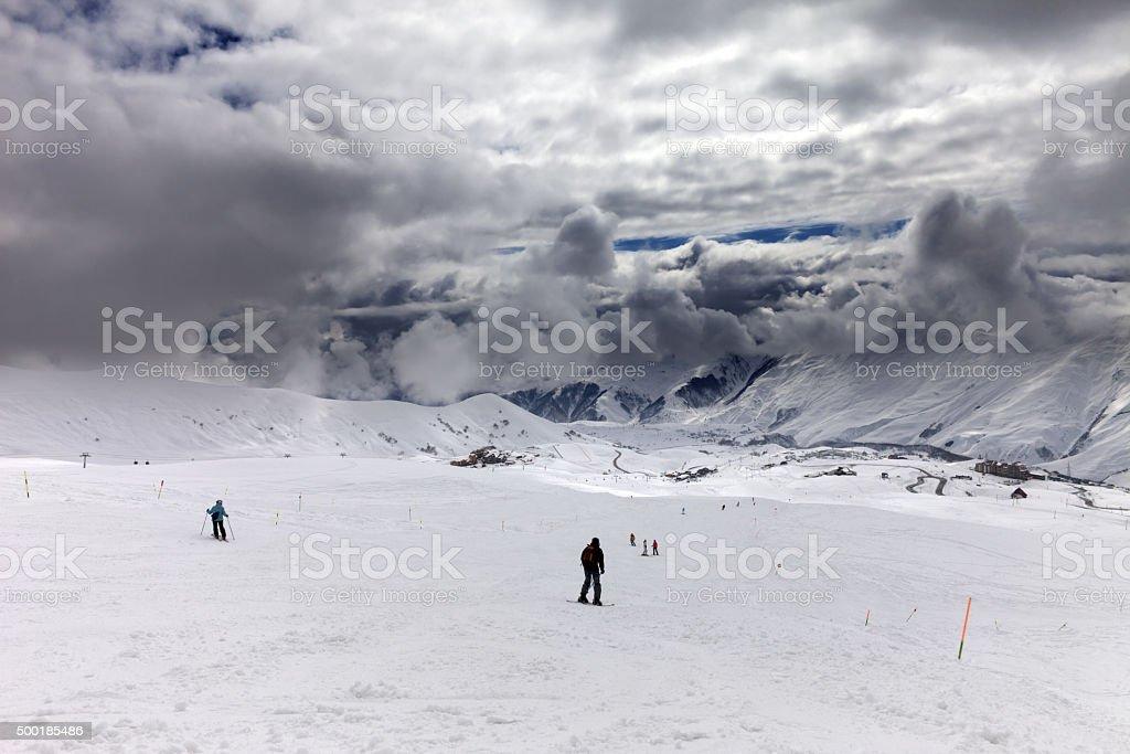 Skiers on ski slope before rain stock photo