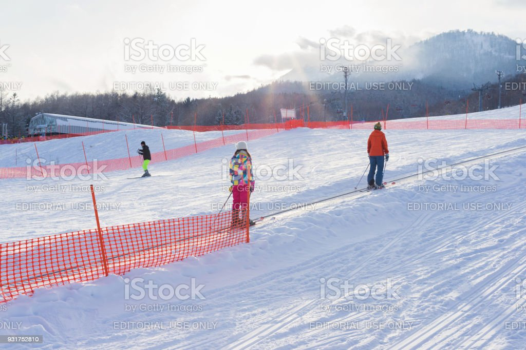 Skiers on snow escalator with mountain and forest background stock photo