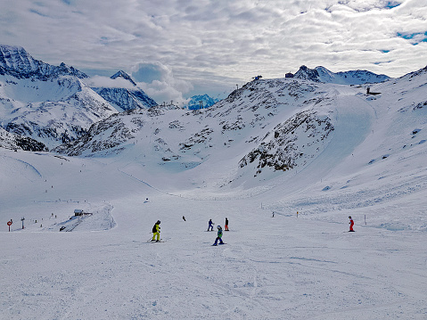 skiers on the ski slope, picturesque alpine landscape