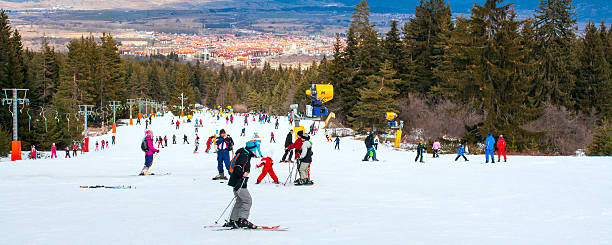 Skiers on the slope , ski lift, mountains view and Bansko stock photo