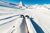 Motion blur in the foreground as a skier descends a piste in the Swiss resort of Zermatt in the Alps, with the peak of the Matterhorn in the distance.