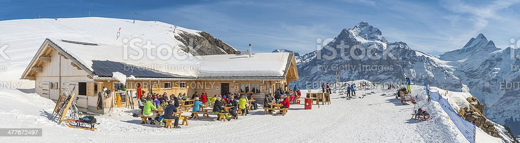 Skiers relaxing at mountain chalet restaurant high in Alps Switzerland royalty-free stock photo