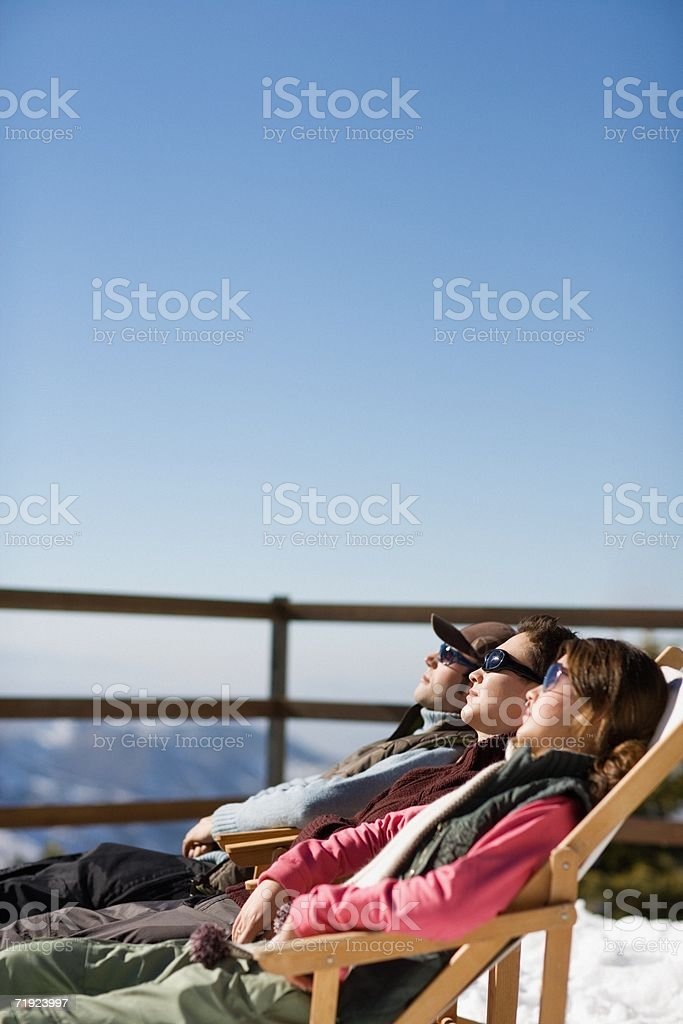Skiers relaxing on deckchairs stock photo
