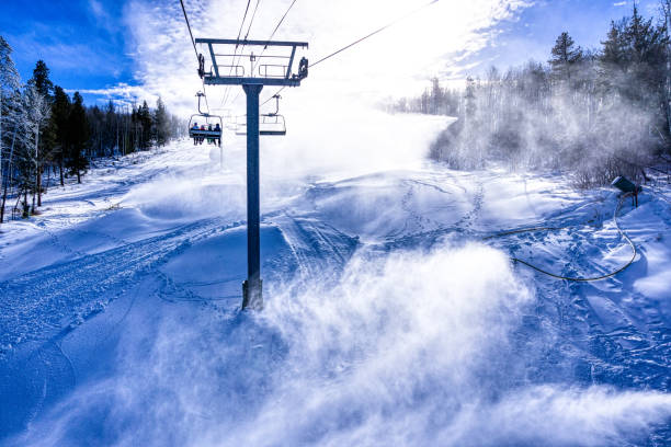 Skiers Riding Chairlift with Snowmaking Skiers Riding Chairlift with Snowmaking - Blowing snow on sunny day. beaver creek colorado stock pictures, royalty-free photos & images