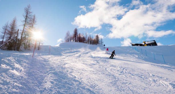 Skiers skiing downhill on mountain sunny landscape stock photo