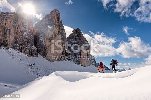 Side view of two young men ski touring in Dolomites, Italy, tre Cime in the background