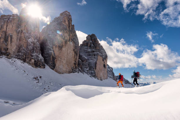 Skiers Touring Around the Cime in Dolomites, italy Side view of two young men ski touring in Dolomites, Italy, tre Cime in the background dolomites stock pictures, royalty-free photos & images