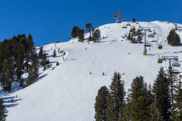 Skiiers and snowboarders enjoying a snow covered mountain stock photo