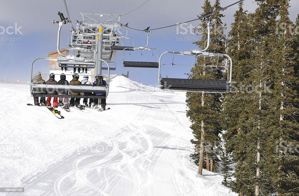 Skiiers and Snowboarders Riding Up a Ski Lift stock photo