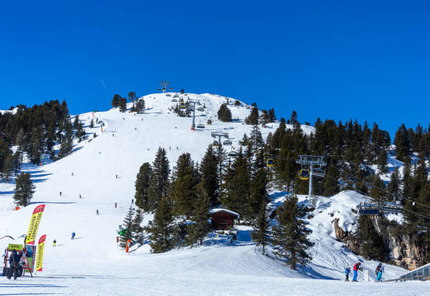 Skiiers enjoy a full sun day using cable cars to get to the top of the mountin stock photo