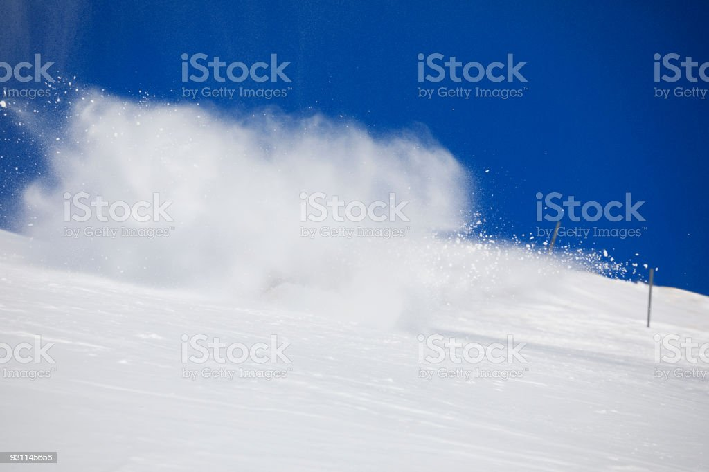 Skiing and snowboarding background. Snow splash. Skier turning on a blue sky day  Ski slope.  Beautiful winter nature. Fresh snow on the top of  mountains.  High mountain landscape  Ski area. stock photo