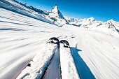 A skier's perspective on a ski piste at speed, with motion blur in the foreground.