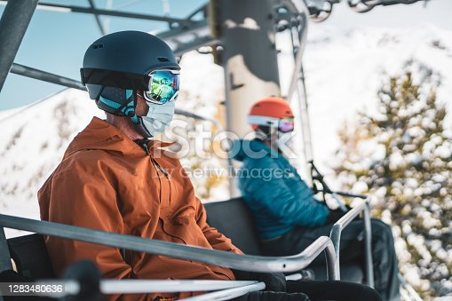 two skiers, one woman and one man with mouth nose mask sitting on ski chair lift with social distance moving up mountain on sunny winter day for a safe skiing, shallow focus on man