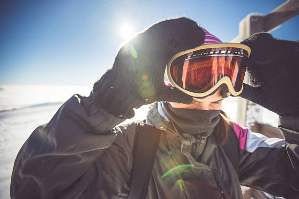 Skiing eyewear Woman putting on skiing goggles ski goggles stock pictures, royalty-free photos & images
