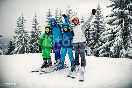 Mother with kids are enjoying skiing on a winter day. Family is cheering to a picture. Sunny winter day. Nikon D850