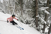 Skiing fresh powder in Whistler, Canada. A women skiing solo in the mountains.