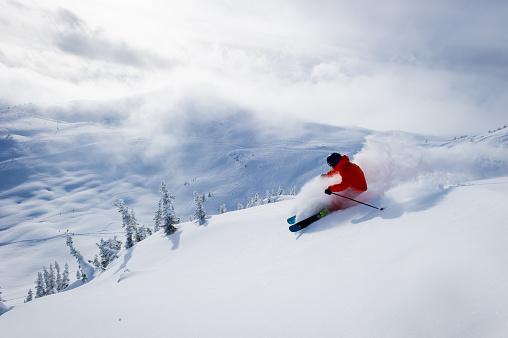Male skiing fresh powder in the mountains. North America's best ski resorts. Canada's top ski destination.