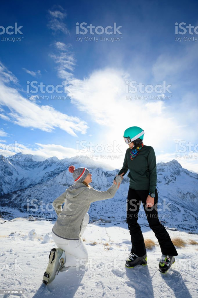 Skiing Happy friends helping eachother on the mountain top Amateur...