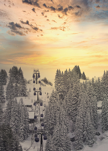 Ski Lift Nasserein Bahn on a snowy day with snowcovered pine trees and mountainrange in the background just before sunset in the skiresort St. Anton, Austria.