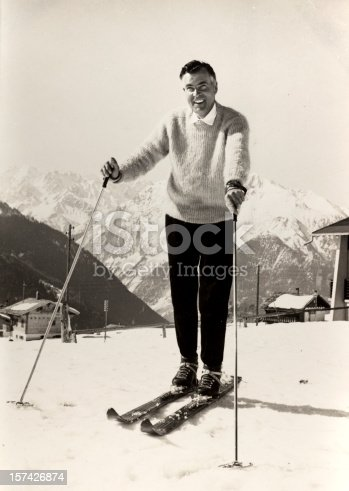 Vintage black and white photograph of a handsome and stylish man on the ski slopes of an alpine resort in the late 1950's.