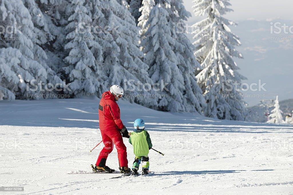 Skiing instructor and child on ski slope stock photo