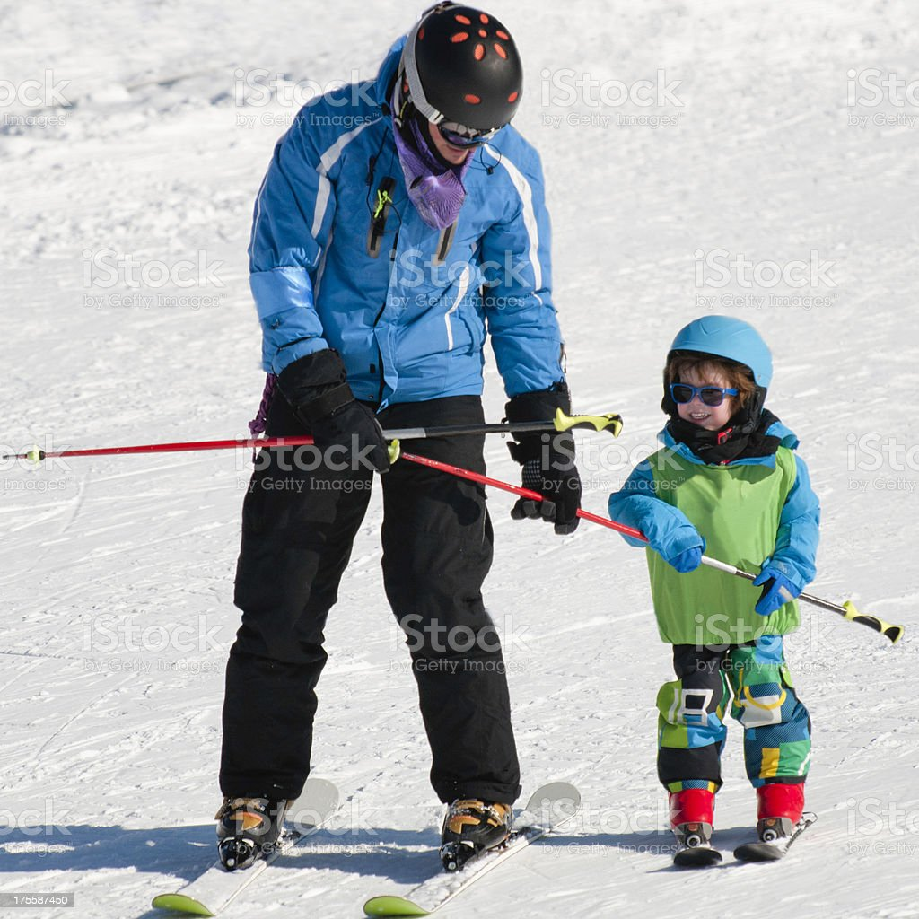 Skiing instructor with smiling little boy stock photo