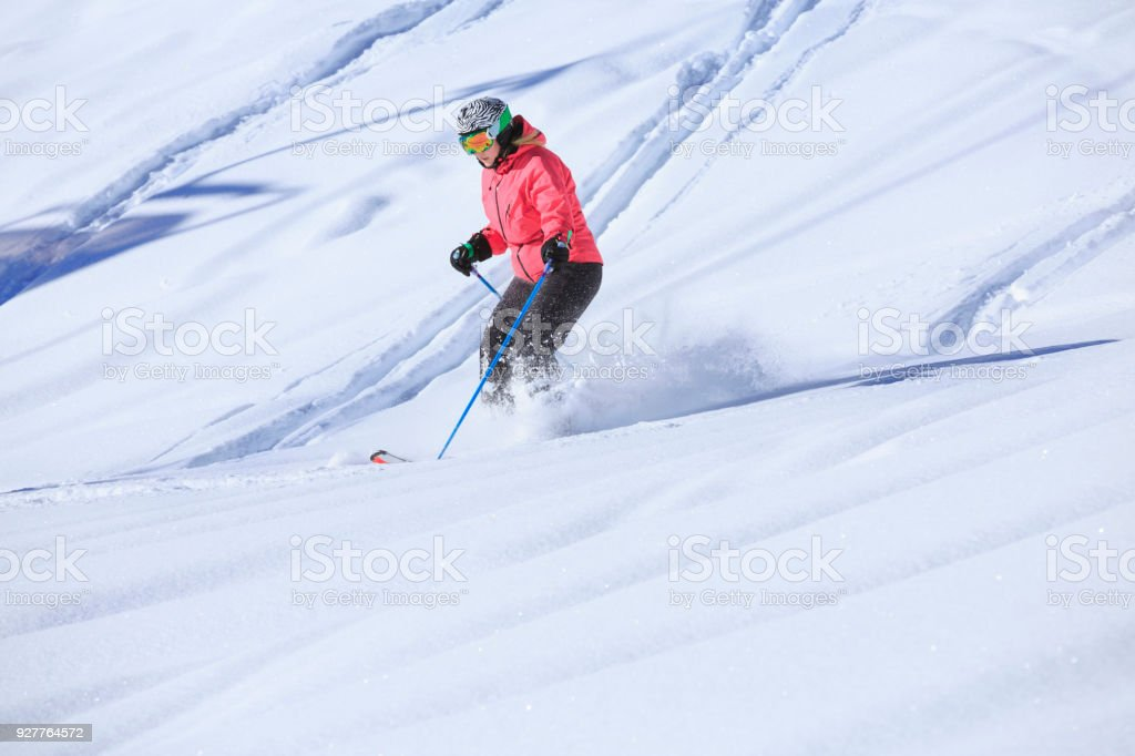 Skiing  Off piste Amateur Winter Sports woman skier skiing in powder snow.   Back country skiing,  at sunny ski resort Dolomites in Italy. stock photo