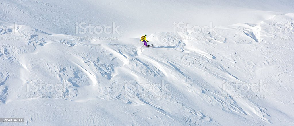 Shot of an off-piste skier skiing on a snow covered mountain ridge...