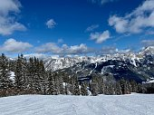 Skiing slope with mountain ridge and cloudy blue sky in background. Tannheimer Tal, Tyrol, Austria