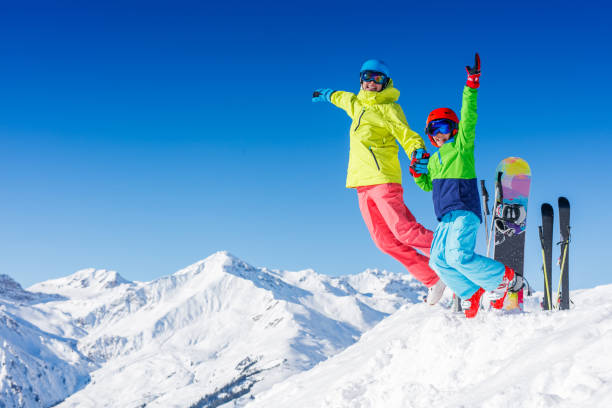 Skiing, winter, snow, sun and fun - kids, boy and girl jumping and having fun in the Alps. Child skiing in the mountains. stock photo