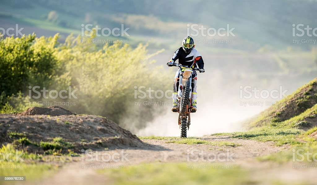 Skilful dirt bike racer riding on a back wheel. stock photo