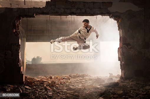 Teakwondo fighter exercising among ruins and performing high kick while being in fly-kick pose.