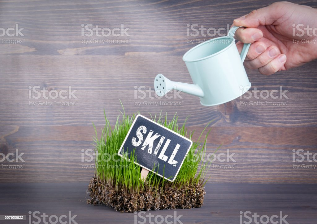 Skill concept. Fresh and green grass on wood background stock photo