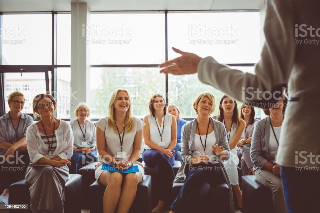 Skill development training for women Group of business women smiling and listening to the speaker during seminar. Women attending a skill development training in conference hall. Adult Stock Photo